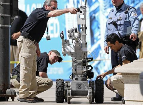 A robot is prepared for observation of a suspicious package tied to a flagpole on the 400 block of North Michigan Avenue.