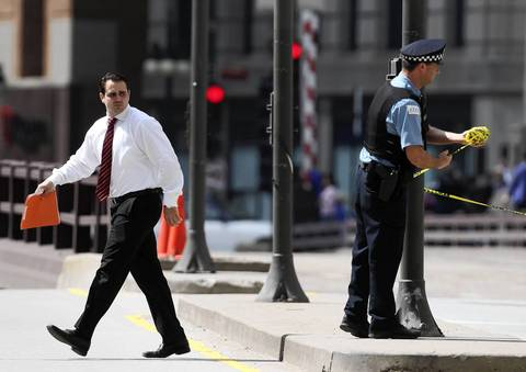 A man crosses the street as a police officer ties caution tape at the perimeter of a suspicious package tied to a flagpole on the 400 block of North Michigan Avenue.
