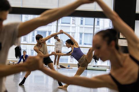 Joffrey ballet dancers Rory Hohenstein, left, and Victoria Jaiani are framed through the arms of other dancers during practice.