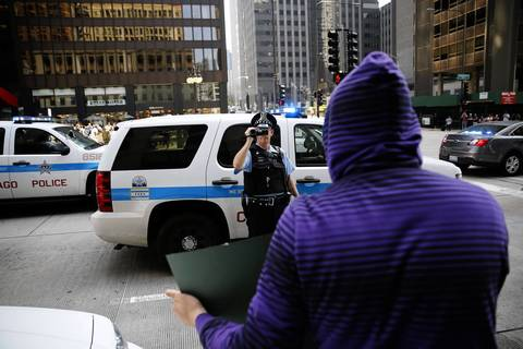 A Chicago police officer videotapes protesters on Michigan Avenue in Chicago as a group of May Day protesters walk south bound on Wednesday, May 1, 2013.