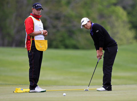 Yani Tseng practices a putt on the green of the 14th hole with her caddie, Paul Fusco, at the Kingsmill LPGA Pro-Am on Wednesday.