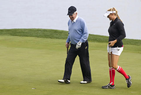 Virginia Tech football coach Frank Beamer walks with Amanda Blumenherst at the 17th hole during the 2013 Kingsmill Championship Pro-Am on Wednesday.