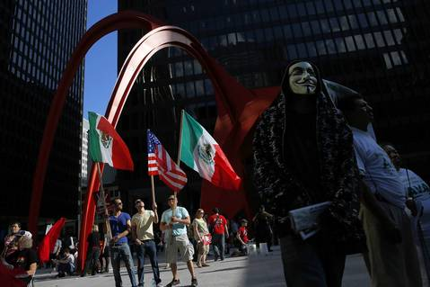 (Left to right) Erick Nava, Luis Moreno and Greg Justus stand hold U.S. and Mexico flags during a May Day march for immigration reform at Federal Plaza, in Chicago.