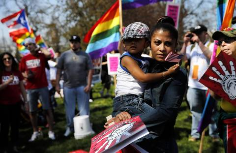 Dina Alvayero, center, holds her three-year-old son, Jose Alvayero, as she joins participants in a May Day march for federal immigration reform in Chicago. Alvayero said she is scheduled to be deported on May 7th.