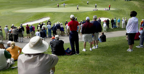 A small crowd gathers around the 7th green as spectators take in the first round of the Kingsmill Championship Thursday.