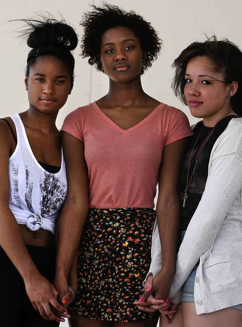Danetria Hutson, from left, Klyn Jones, and Kyra Caldwell pose outside King College Prep in Chicago. The three teens were with Hadiya Pendleton when she was shot and killed on Jan. 29, 2013.