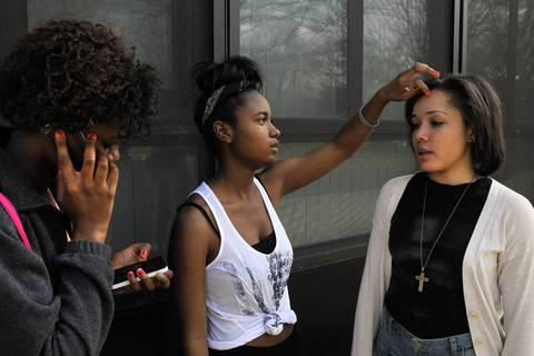 Danetria Hutson, center, primps Kyra Caldwell as Klyn Jones talks and texts on phones outside King College Prep in Chicago.