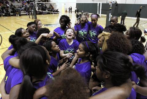 Kyra Caldwell, center, rallies with teammates before playing in an anti-violence volleyball tournament in honor of slain friend Hadiya Pendleton at Hope Academy Athletics Center in Chicago.