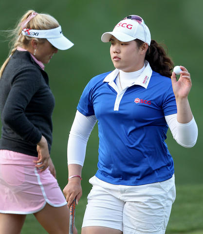Ariya Jutanugarn waves to the crowd after completing second round of the Kingsmill Championship Friday in Williamsburg. Jutanugarn finished 7 under in first place.