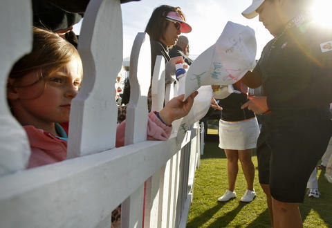 Josie Briggs, 5, left, of Richmond waits to get the autograph of Ariya Jutanugan, right, after Saturday's third round of the LPGA Kingsmill Championship.