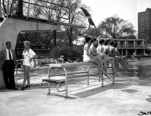 Dick Noel, left, popular recording artist and vocalist, model Celeste Ravel, second from left, and Ken Golden on the high dive enjoy opening day at the Edgewater Beach Hotel pool. On the lower diving board are members of the Lorelei Swim Club, a synchronized swim team at Northwestern University, April 28, 1955.