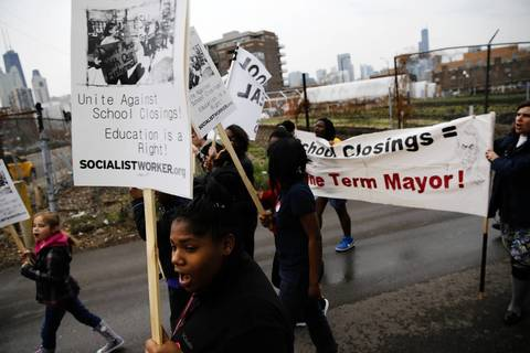 Students, parents and community members from Manierre Elementary School at 1420 N. Hudson Ave. in Chicago rally as they make their way to Edward Jenner Elementary Academy of the Arts, located at 1119 N. Cleveland Ave. Manierre is being closed and consolidated with Jenner school. The parents of Manierre school are concerned with their students crossing the busy Division Street intersection into rival gang territory to attend Jenner.