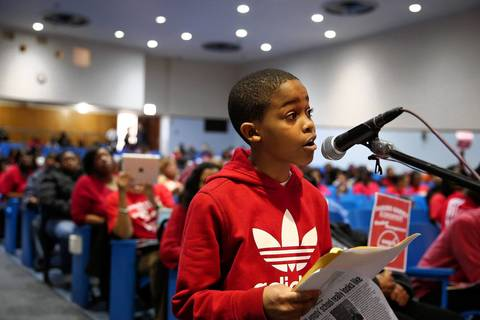 Asean Johnson, 9, a third grader at Marcus Garvey Elementary, speaks in defense of his school during a community meeting at Harlin High School in Chicago.