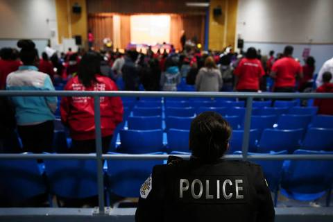 A Chicago police officer keeps watch over the room as community members, mostly supporting Marcus Garvey Elementary, speak to Chicago Public School Chiefs Tony McPhearson, Tom Tyrrell, Karen Saffold and Commander James Gibson of the Chicago Police Department, in defense of their school during a community meeting at Harlin High School in Chicago.