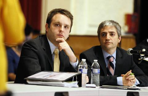 Chicago Public Schools administrators Adam Anderson, left, and Todd Babbitz listen to parents speak about the planned closing of Calhoun Elementary School during a CPS feedback meeting at Ruby High School.