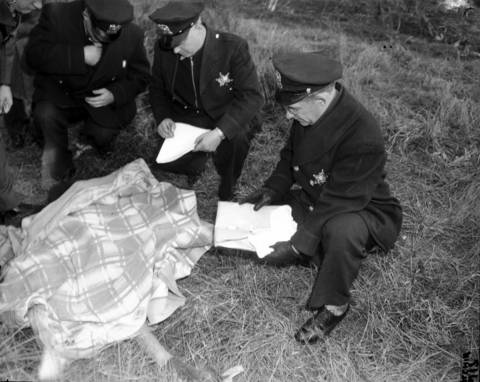 "Police examine cigarette butts found at the crime scene of the murder and rape of 10-year-old Roberta Rinearson. Also found near the scene was a man's handkerchief with a monogram ""P"" in a corner which was found on the opposite side of the road. The handkerchief became a central clue in Rinearsons death."