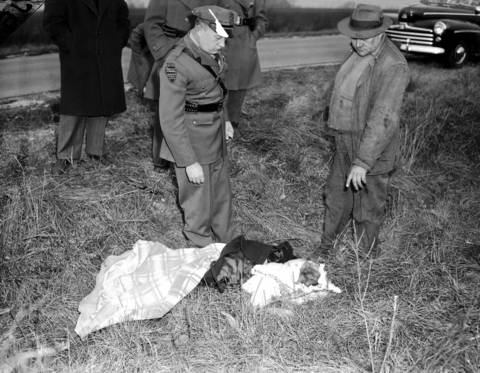 Police officer John A. Peters, left, and another man examine the body of Roberta Rinearson at the crime scene on Dec. 18, 1948. Authorities never found the brown loafer shoes Roberta had been wearing.