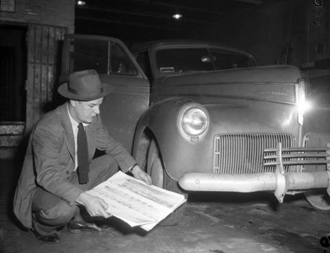 Joseph Haas, of the Chicago Crime lab, checks the tire marks taken at the murder scene against tires of a car belonging to Harold Poull which was found in La Grange on Feb. 12, 1949. Haas was working on the murder case of Roberta Rinearson. For years, the police followed up on many leads trying to find Roberta's killer.