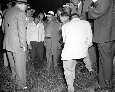 George Lettrich Jr., center, stands on Aug. 13, 1950 at the location where he confessed to raping and murdering 10-year-old Roberta Rinearson. He is handcuffed to Lyons Police Chief Ralph White.