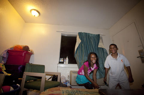 Teá, 10, and Titus, 8, dance in the room where their family lives at the Centerstone Inn in Newport News.