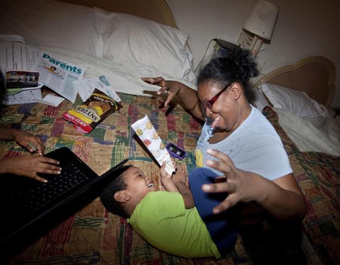 Eva Williams plays with her four-year-old son, Tim, as they wait for a delivery of Chinese takeout to their room at the Centerstone Inn in Newport News on March 7. Williams, her husband and their six children have lived at the hotel since August 2012.