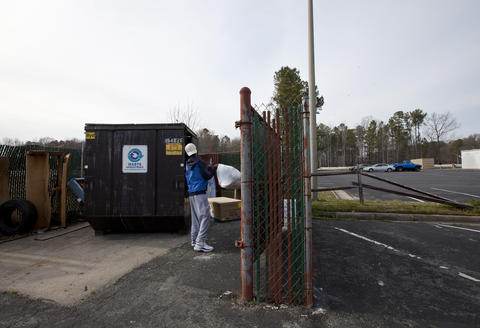 Terrell, 13, throws out a bag of trash in the dumpster behind the Centerstone Inn after arriving home from school on March 15.