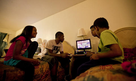 (From left) Teá, Terrance, Terrell and Tim play video games as they wait for an evening delivery of Chinese food to the Centerstone Inn on March 7.
