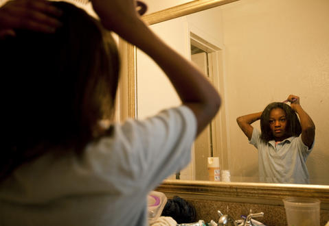 Teá fixes her hair in the bathroom mirror before the bus arrives to take her to Newsome Park Elementary on April 10.