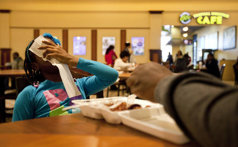 Teá shows her frustration as her family shares her order of chicken at the food court in Patrick Henry Mall on Saturday, March 30.