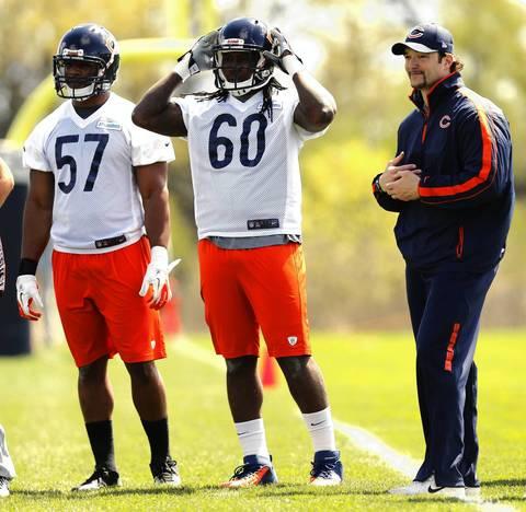 Linebackers Jonathan Bostic and Khaseem Greene (60) watch passing drills with linebackers coach Tim Tibesar.