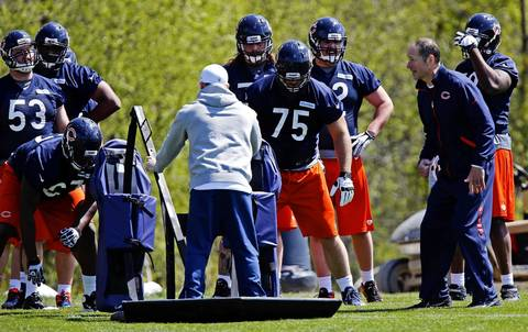 Offensive coordinator/offensive line coach Aaron Kromer works with Kyle Long and other linemen.