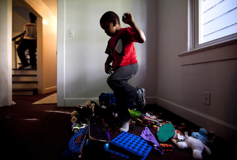 Tim empties a basket of toys on the floor as the Williams family moves into their new house on May 3.