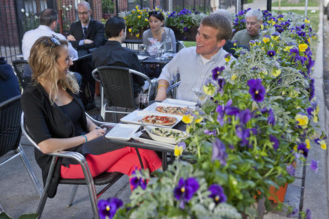 Flower-filled planters line the sidewalk cafe at Italian-inspired Boystown bar and restaurant Taverna 750.