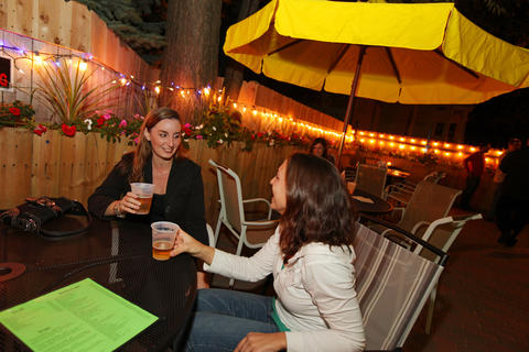 The backyard patio at Logan Square bar hangout features umbrellas, lights and planter-lined fence.