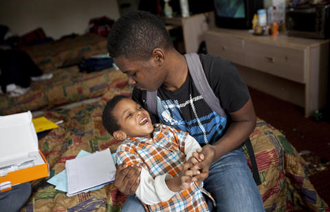 Tim, 4, and Terrance, 15, play on the bed after arriving home from school on March 15.