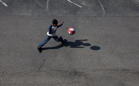 Titus plays basketball in the parking lot of the Centerstone Inn on a spring Saturday morning.