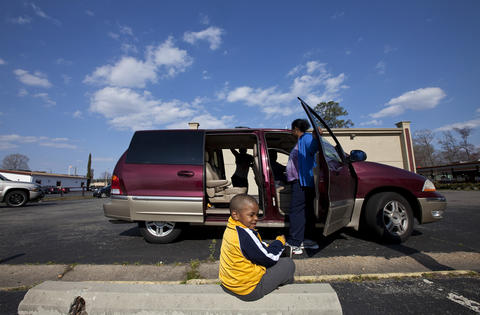 Tim sits on a curb to put on his shoes as his family piles into the van to go to the food court at Patrick Henry Mall for lunch on Saturday, March 30.