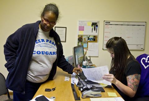 Eva turns in an application for housing at Bernie Anderson Rentals in Hampton during a hectic afternoon of errands on April 25.