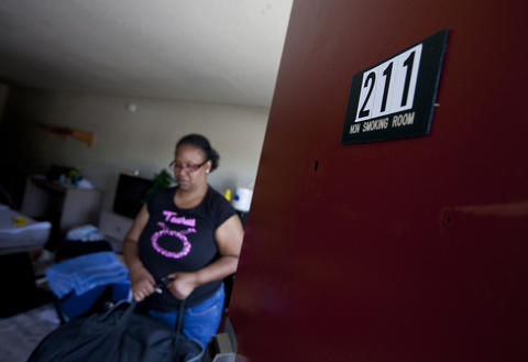 Eva carries bags of clothes to move out of the room where her family has lived at the Centerstone Inn since August 2012.
