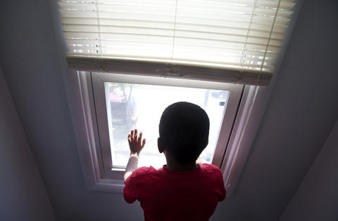 Tim looks out of an upstairs window at his family's new house in a Southeast Newport News neighborhood.