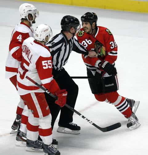Dave Bolland is held back from Detroit Red Wings' Jakub Kindl (4) and Niklas Kronwall.