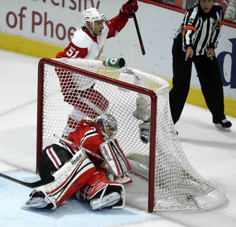 Corey Crawford and the Red Wings' Valtteri Filppula react to Brendan Smith's go-ahead goal.