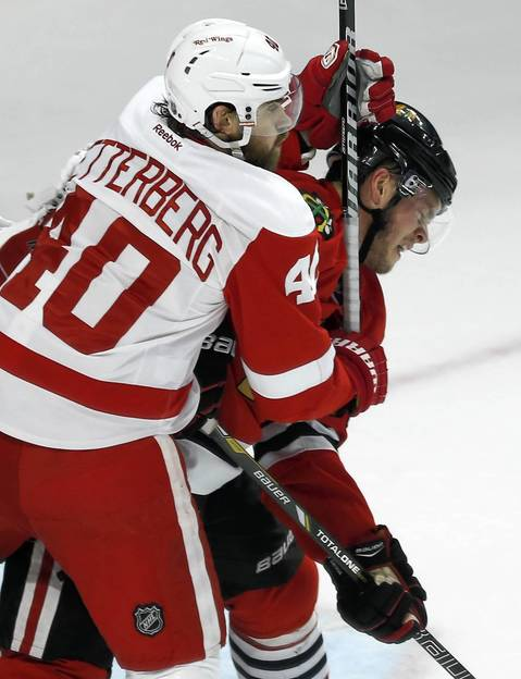 Jonathan Toews is checked by Detroit Red Wings' Henrik Zetterburg.