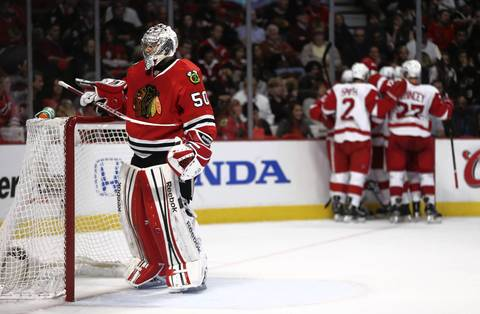 A dejected Chicago Blackhawks goalie Corey Crawford (50) reacts as the Detroit Red Wings celebrate a goal by defenseman Brendan Smith.