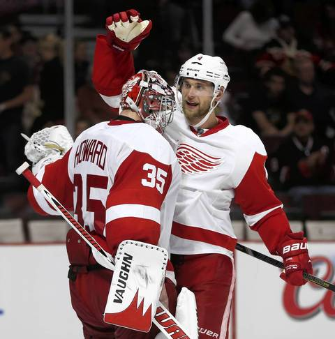 The Red Wings' Jakub Kindl congratulates goalie Jimmy Howard after beating the Blackhawks in Game 2.