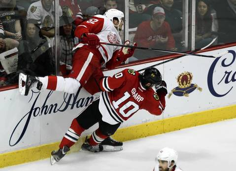 Patrick Sharp falls to the ice after hitting the Red Wings' Jonathan Ericsson.