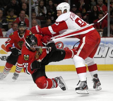 The Red Wings' Johan Franzen knocks Michal Rozsival to the ice.