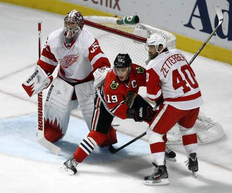 Jonathan Toews tries to establish position against the Red Wings' Henrik Zetterberg and Jimmy Howard.