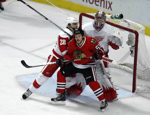 Andrew Shaw tries to establish position against the Red Wings' Carlo Colaiacovo and Jimmy Howard.