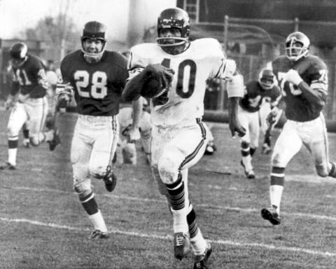 Gale Sayers was one of football's most explosive runner from 1965 to 1971. In a preview of things to come, the halfback scored touchdowns on long punt and kick returns and a pass play in his first preseason game. During the regular season, he scored a record-tying six touchdowns on a muddy field against the 49ers. From that rookie year, Sayers still has the team record for most touchdowns in a season with 22. He rushed for close to 5,000 yards and scored 336 points over a short career and was the NFL's all-time leader in kickoff returns at the time of his retirement. He was elected to the Hall of Fame in 1977.